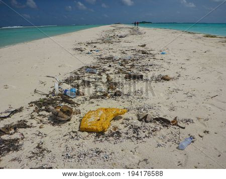 A beach in the Maldives covered with washed up rubbish spoiling it
