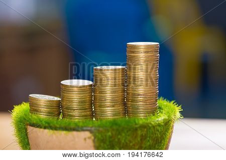 Stack Of Gold Coin On Artificial Grass In Pot, On Wooden Table.
