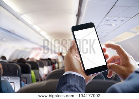 Airplane passenger using smart phone on plane. Businessman touching blank screen mobile phone at airplane. for graphics display montage.