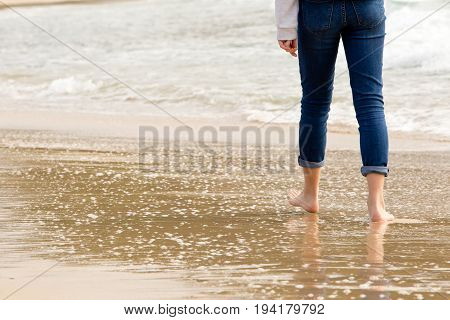 Solitary person walking - wading in incoming waves on beach poster