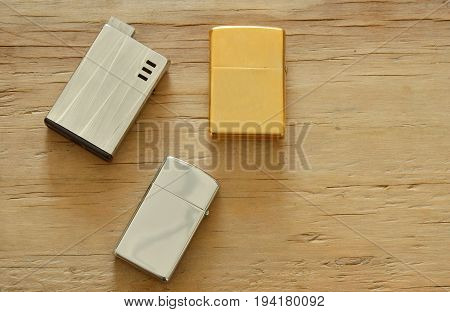 silver and gold lighter on wooden board