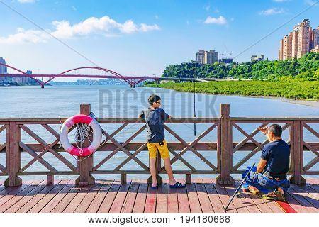 TAIPEI TAIWAN - MAY 29: Fisherman and his son fishing in the river in Taipei near the famous Guandu bridge on May 29 2017 in Taipei