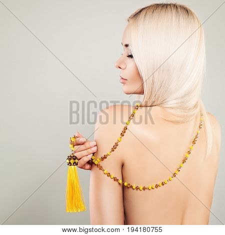 Perfect Blonde Woman Fashion Model with Blonde Hair and Amber Necklaces