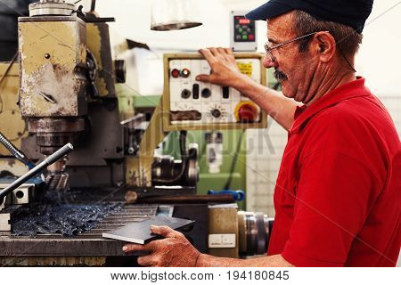 Worker in big industrial company producing parts on his machine.