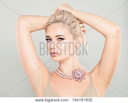 Beautiful Glamorous Blonde Woman Fashion Model with Pink Flower Necklaces and Blonde Hairstyle
