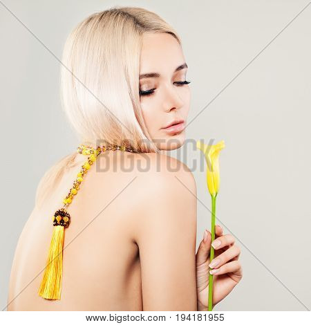 Beautiful Blonde Woman Fashion Model with Yellow Flower Blonde Hair and Amber Necklaces. Blonde Beauty