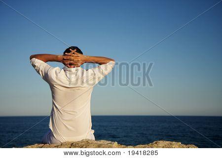 Man sitting on rocks looking and enjoying seaside view