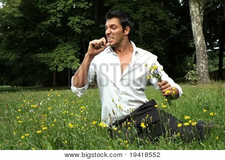 Young man sneezing in a green park