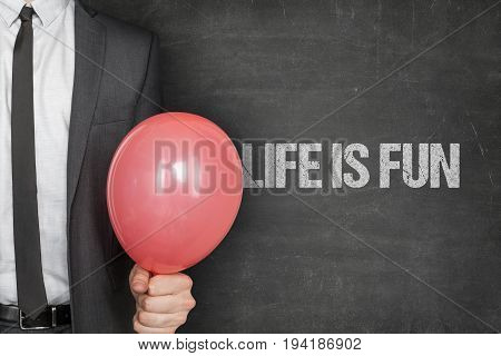 Midsection of businessman holding red balloon with life is fun text on chalkboard