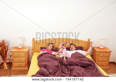 Young family of three people mom, dad, girl awaking in bed at home in the morning