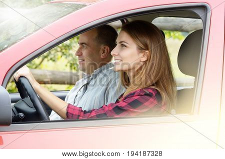 Young happy woman having driving lesson with instructor