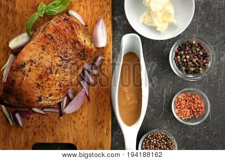 Cutting board with delicious turkey, spices and gravy boat on grey table