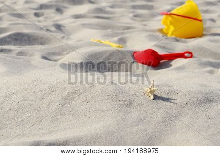 Bright yellow plastic sandbox toys on the sand