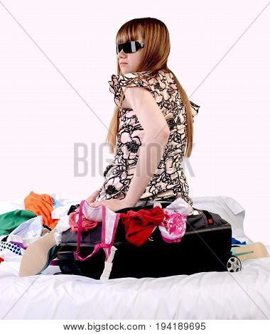 Girl is sitting on a suitcase with things preparing for a long journey