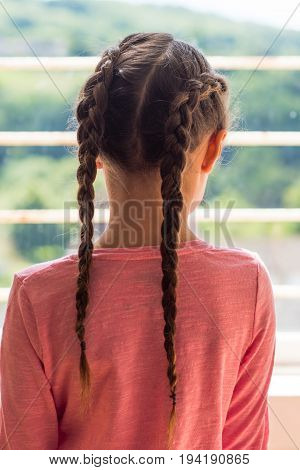 Girl with Dutch plaits looking out of window from behind. Young child with brown hair braided in a pink top