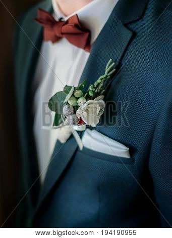 Closeup of white boutonniere pinned to groom's green jacket