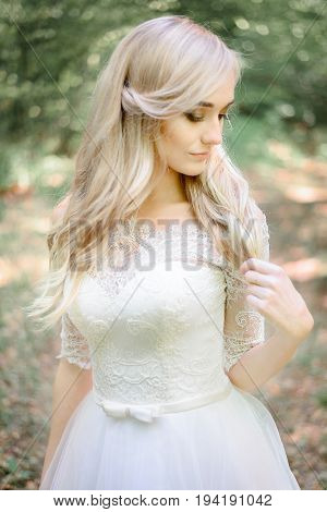 Bonny Blonde Bride Touches Her Hair Delicately While Standing In The Forest