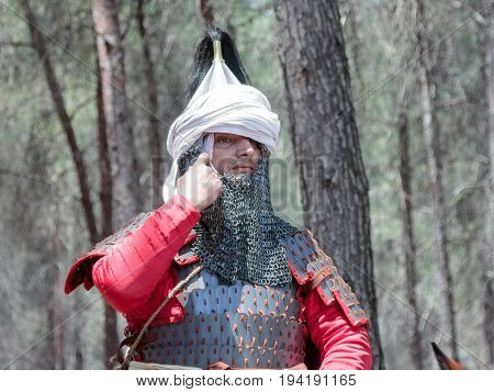 Tiberias Israel July 01 2017 : Participants in the reconstruction of Horns of Hattin battle in 1187 depicting Saladin corrects the helmet in the camp before the campaign near TIberias Israel