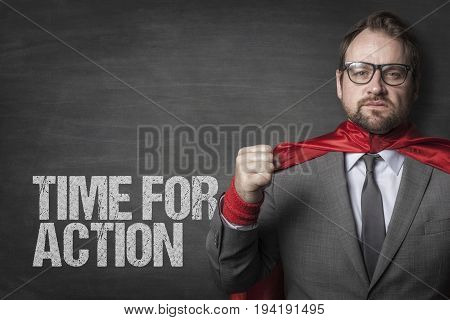 Determined businessman wearing cape standing by time for action text on blackboard