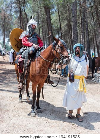 Tiberias Israel July 01 2017 : Participants in the reconstruction of Horns of Hattin battle in 1187 one sits on a battle horse and the second one holds a horse in the camp before the campaign near TIberias Israel