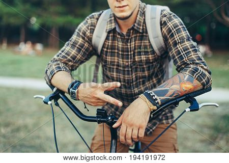 Young Man Shows A Sign Of Peace Or Victory Sitting On A Bicycle On Green Summer Meadow