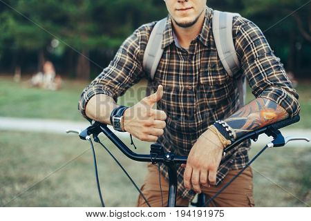 Young Man Is Making Thumb Up By Hands Sitting On A Bicycle On Green Summer Meadow