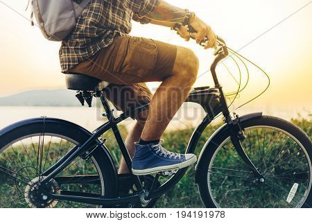 Unrecognizable Young Hipster Man Is Cycling Along The Shore Against The Backdrop Of The Sunset Vacation Holiday Activity Concept