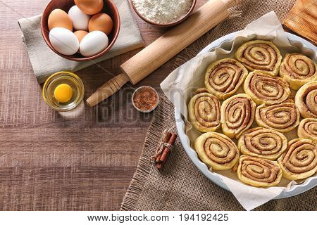 Raw cinnamon rolls in baking pan and ingredients on kitchen table