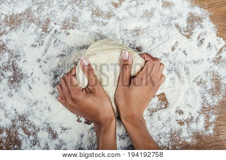 Cropped Shot Of Hands Kneading Dough On Wooden Table Top