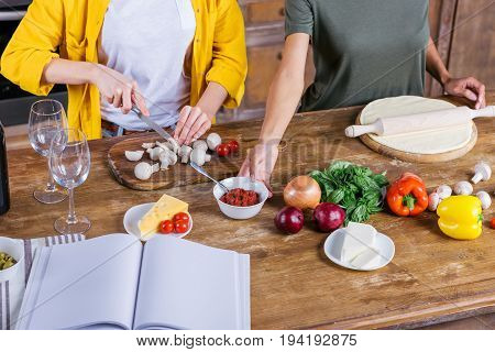Cropped Shot Of Young Women Cooking Pizza While Standing Together At Kitchen Table With Blank Cookbo