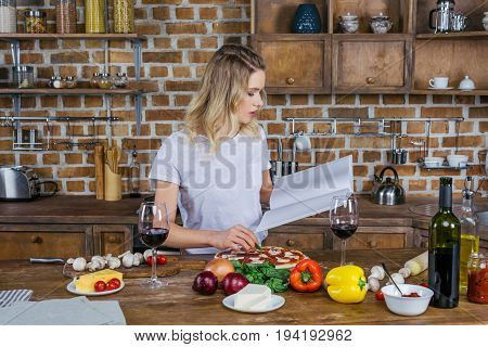 Attractive Blonde Woman Holding Cookbook While Preparing Pizza In Kitchen