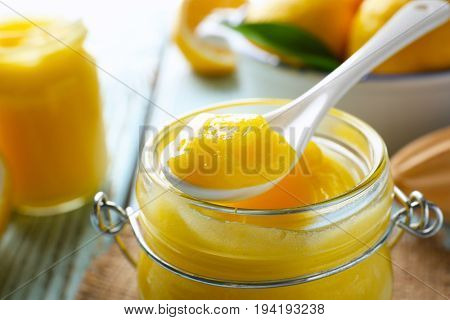 Glass jar and spoon with delicious lemon curd on table, closeup