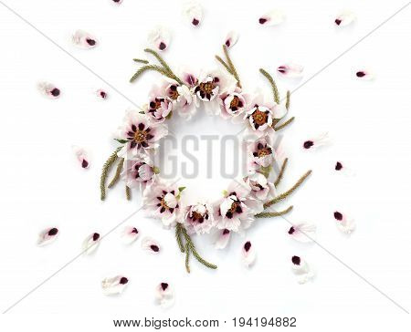 Round floral frame made of white peonies big evergreen branches and falling petals on white background. Top view flat lay.