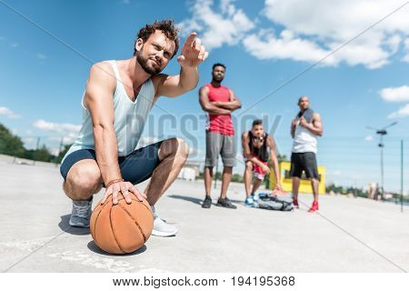 handsome man pointing away while sitting on court with basketball ball