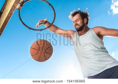 low angle view of basketball player throwing ball into basket against blue sky