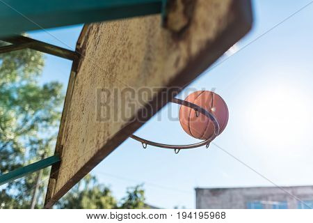 close up view of basketball ball falling into basket against blue sky