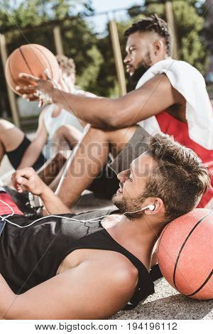 multiethnic basketball team resting after game on basketball court together