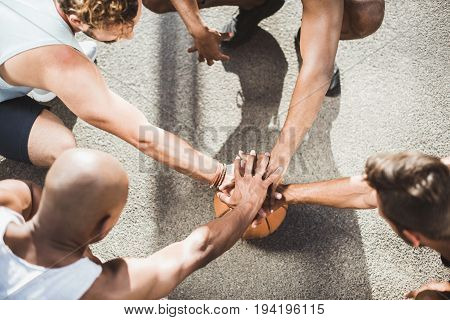 overhead view of basketball team holding hands on basketball ball on court