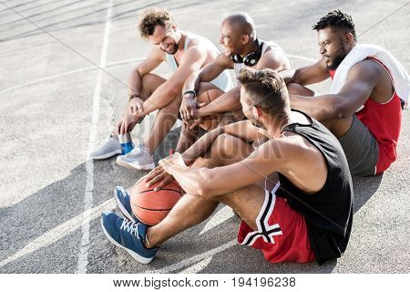 Multiethnic Basketball Team Sitting After Game On Basketball Court Together