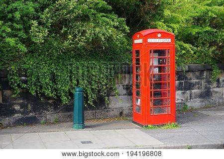 A vintage red British telephone booth stands by the roadside in Edinburgh Scotland. Many of these iconic booths have been retired from service and are now being repurposed as sales kiosks and other uses.