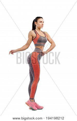 Beautiful young sportive woman fitness fit-fitting clothes posing on white isolated background. Fitness model