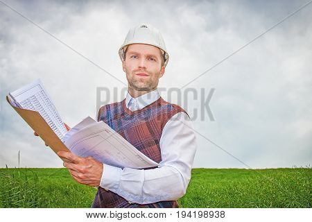 Engineer builder architect with project documentation in hands in white helmet. Engineering concept of construction, work of professional, technical specialist