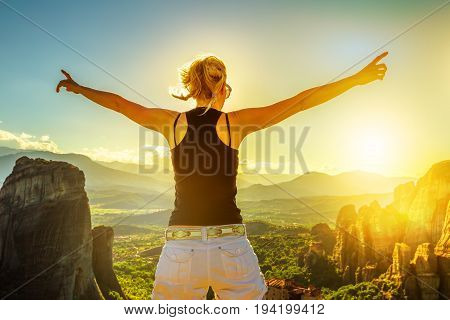 Traveler woman with open arms at sunset in Meteora valley in Thessaly, Greece. Happy female hiker with sun in the face. Panoramic view from best view point Psaropetra. Tourism in Europe.