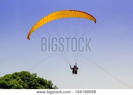 Paragliding above hill in bright summer day