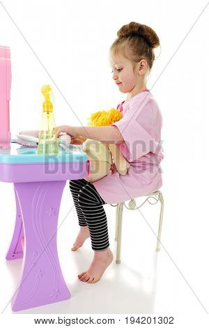 An adorable preschool in an over-sized cosmetology smock, sitting at a toy hairdresser's station with a doll on her lap.  On a white background.