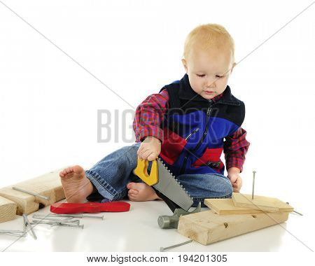 An adorable toddler playing tool-man trying to saw while holding the tool upside-down. Nails, a hammer and blacks of wood surround him.