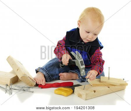 An adorable toddler carefully setting the nail he's getting ready to hammer.  On a white background.