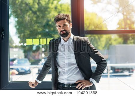 portrait of confident businessman standing at window during work