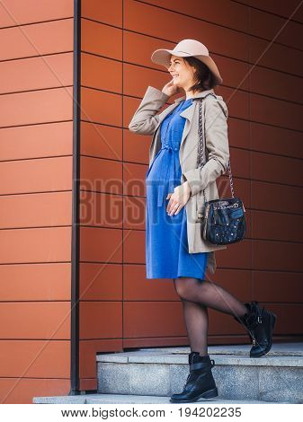 Shooting a beautiful pregnant woman in a modern city. Pregnant woman in a trench coat and hat