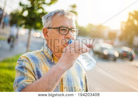 Senior man is drinking water in the city.